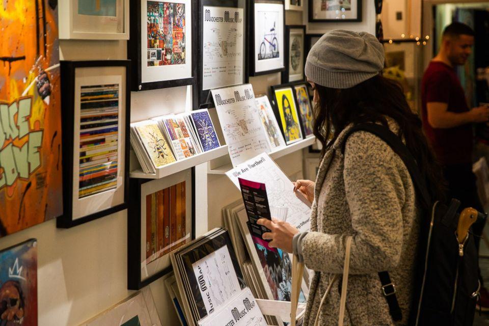A woman browsing art prints at Afflecks