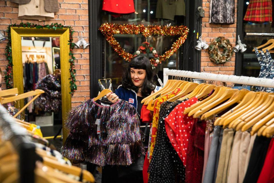 A woman browsing vintage clothing at Afflecks