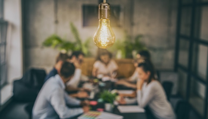 a blurred picture of seven people working together around a desk with a light bulb in focus at the front of the shot