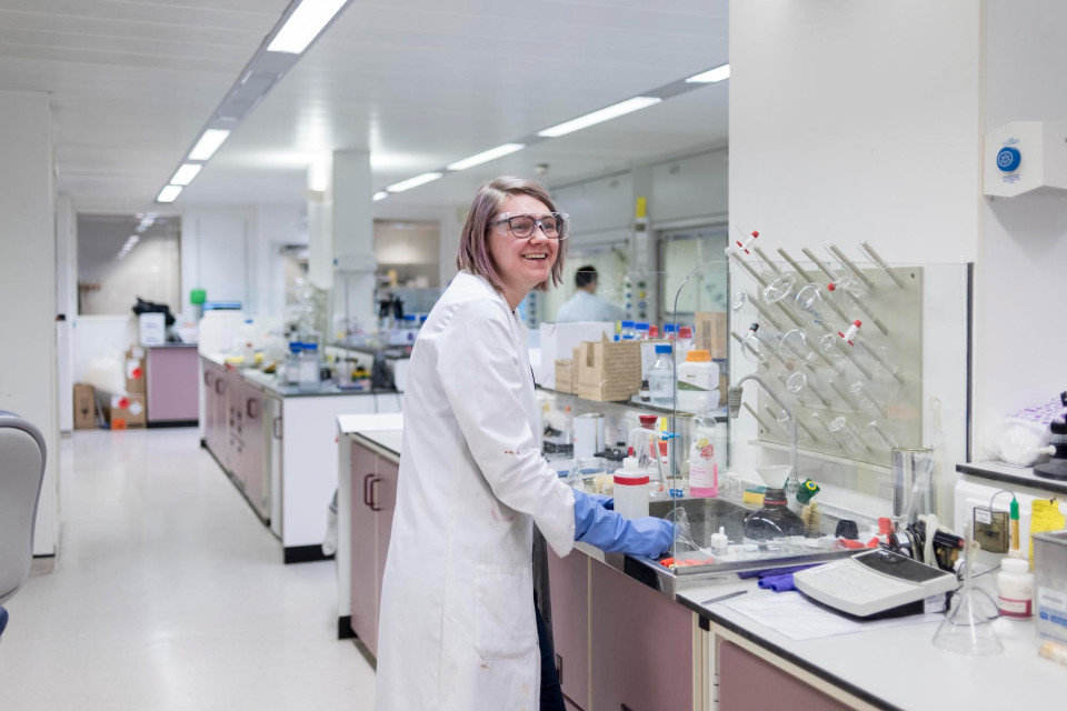 A woman smiling in a lab wearing protective glasses
