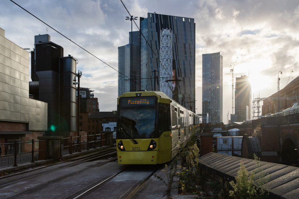 A yellow Metrolink tram heading to Piccadilly with tall buildings and the sun setting in the background