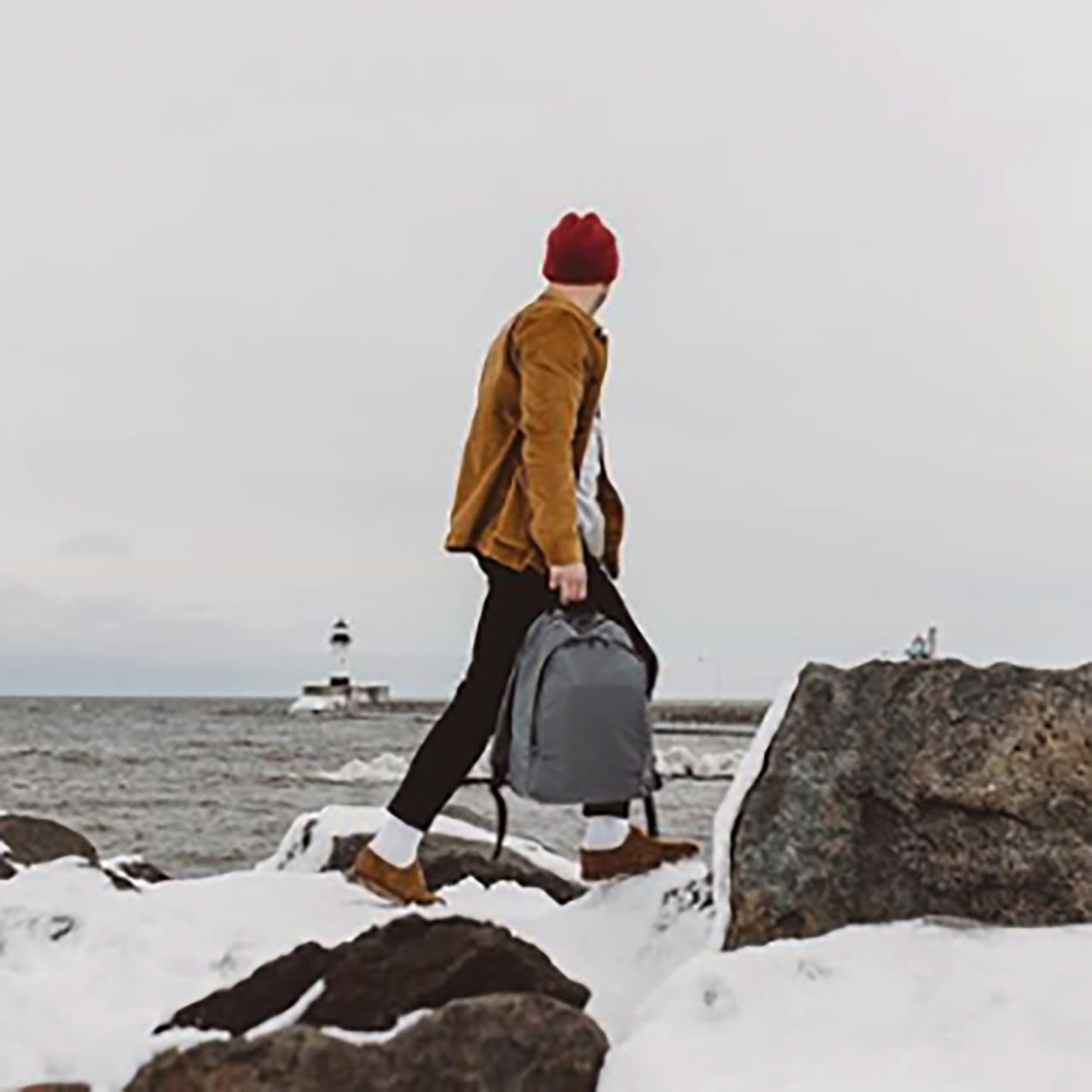Man in a red beanie with a grey Away backpack walking on snow covered rocks while gazing at a lighthouse.