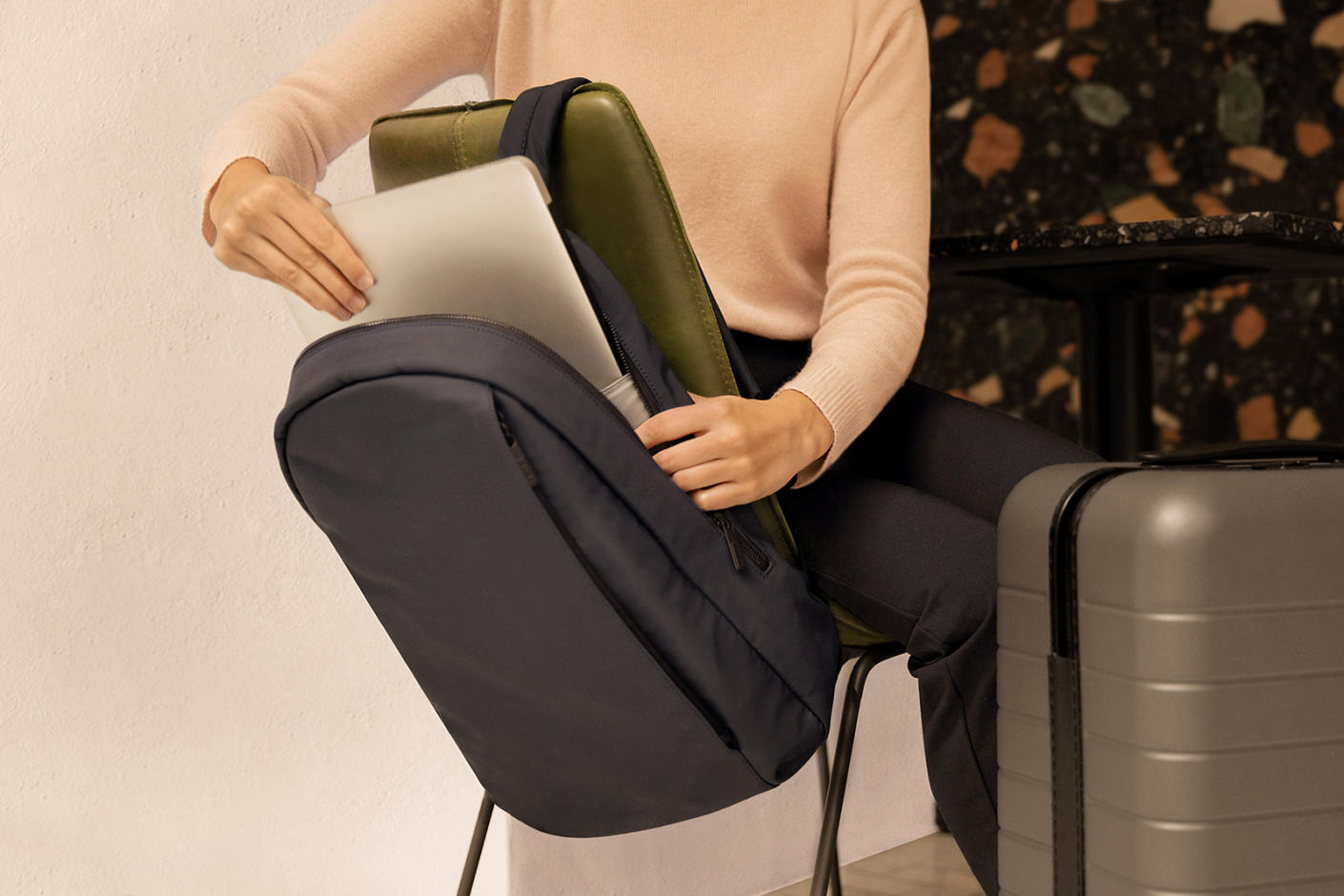 A person sitting on a chair, taking out a laptop from a gray small backpack with a gray hard shell suitcase next to her.
