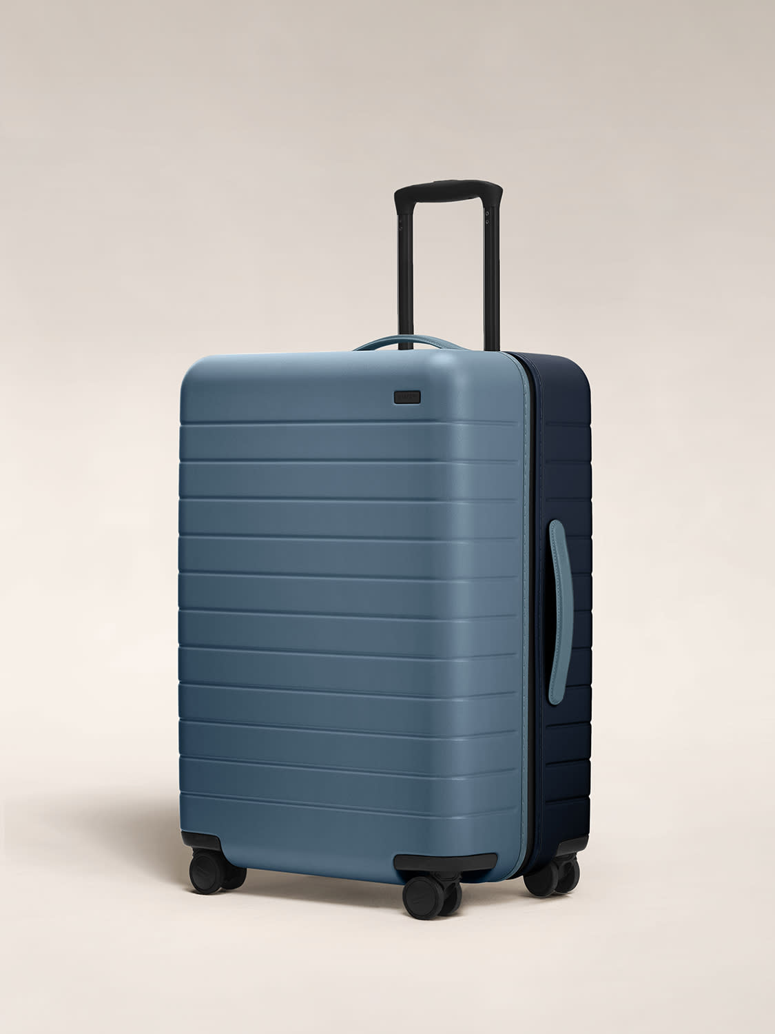 Angled view of the hardside Medium suitcase in Coast/Navy