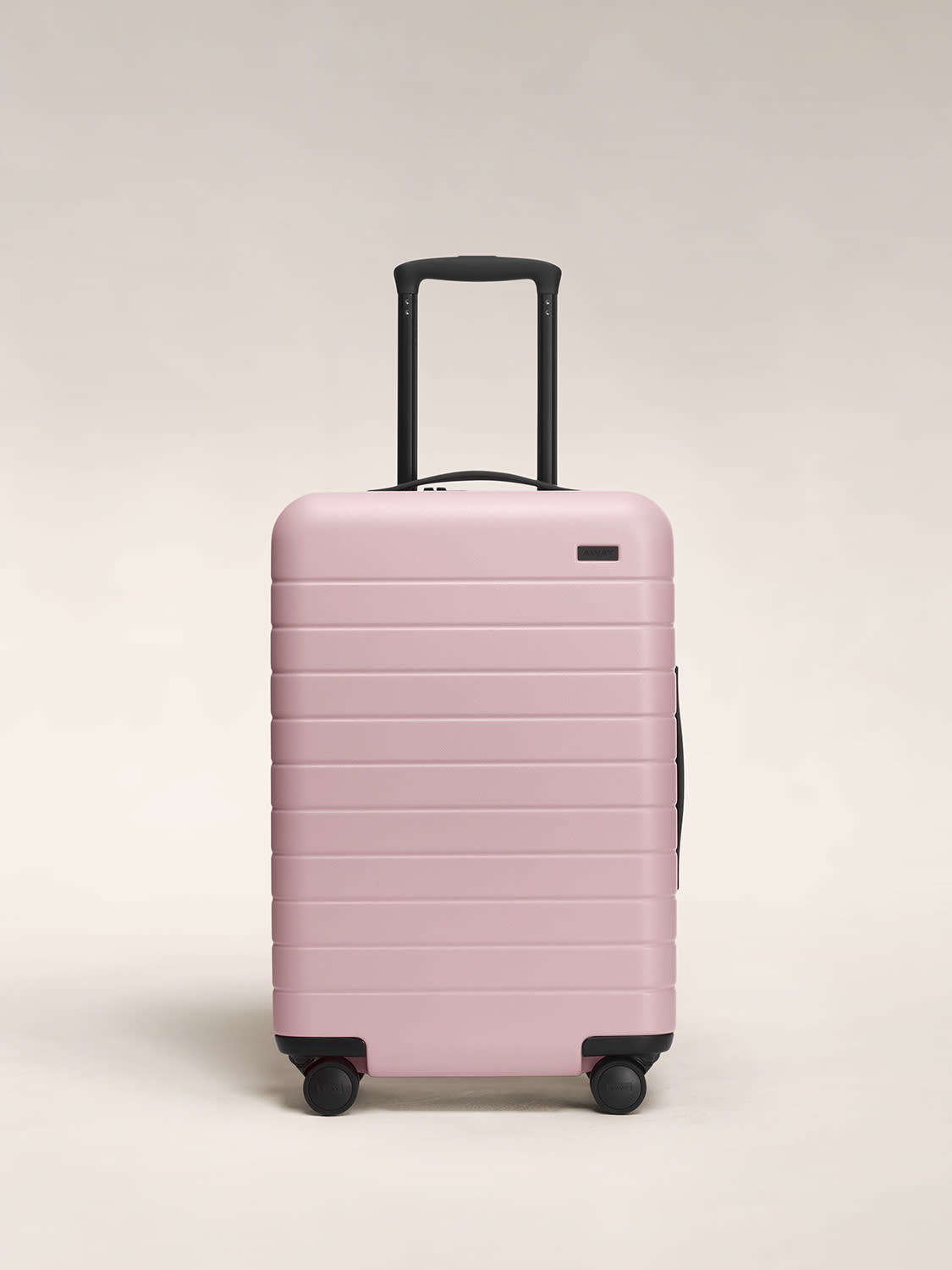 Front view of the Away Blush Bigger Carry-On hardside showing raised handle.