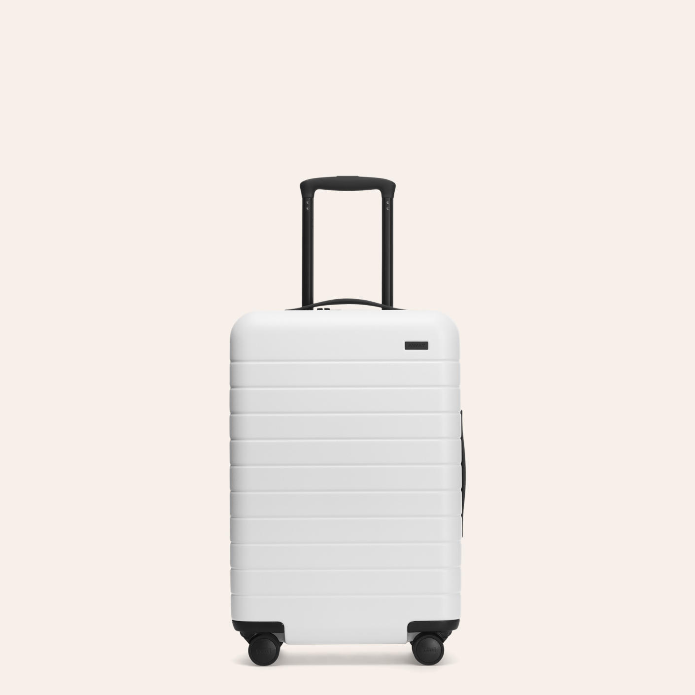 The Away Bigger Carry-On in white shown from front with raised telescoping handle