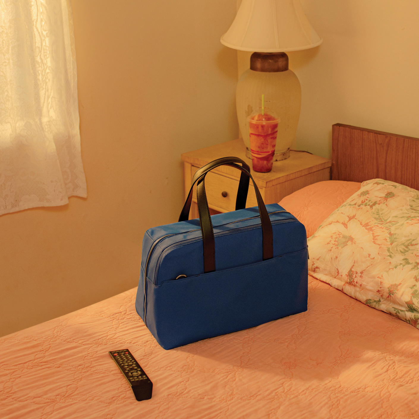 A blue duffle bag with black straps raised, on a neatly made bed and a TV remote on the side.