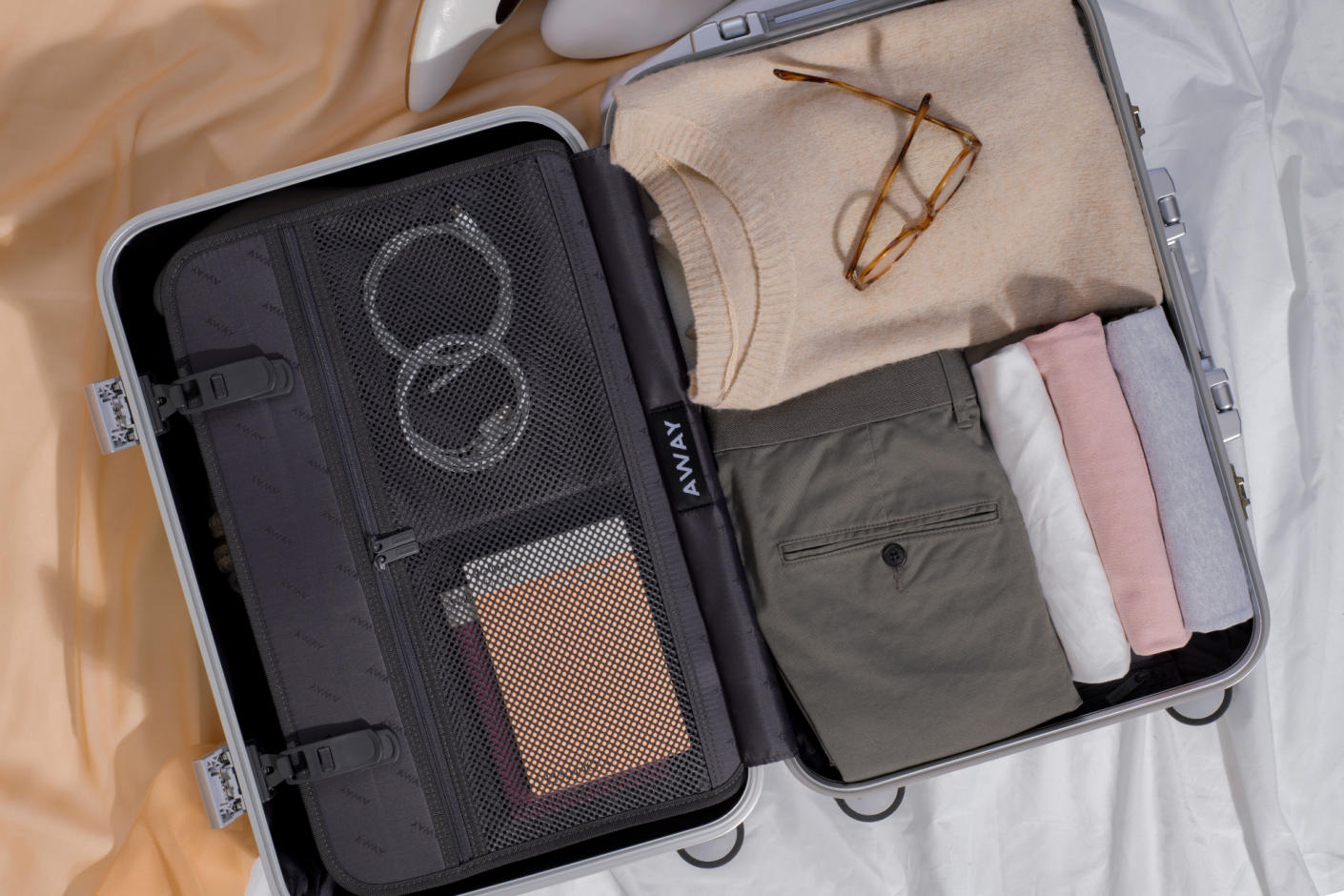 An Aluminum suitcase opened to reveal a clip in mesh pocketed panel folded clothes on the right side.
