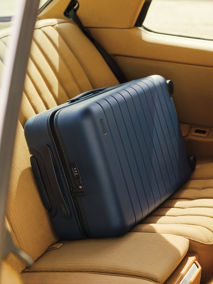 Away navy carry-on suitcase laying on its side in the backseat of a car with sand upholstery.
