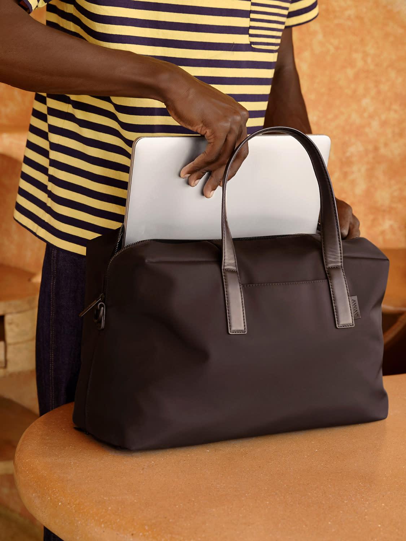 A man putting a laptop into a black travel work bag (Away Everywhere bag).