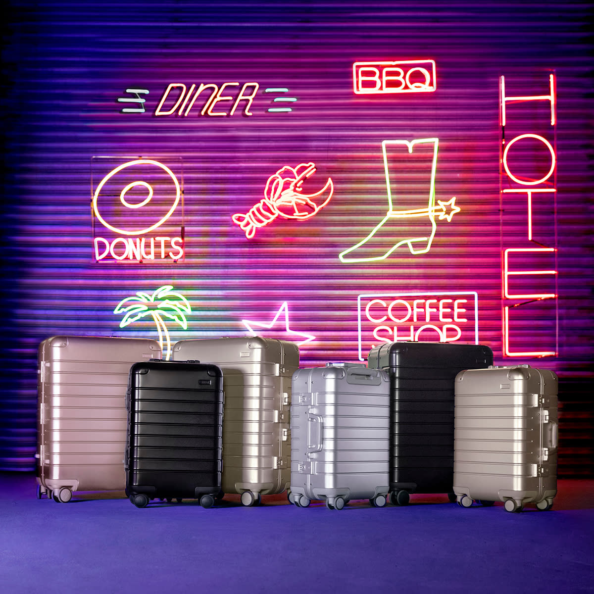 The Away Aluminum luggage collection displayed against a neon background.