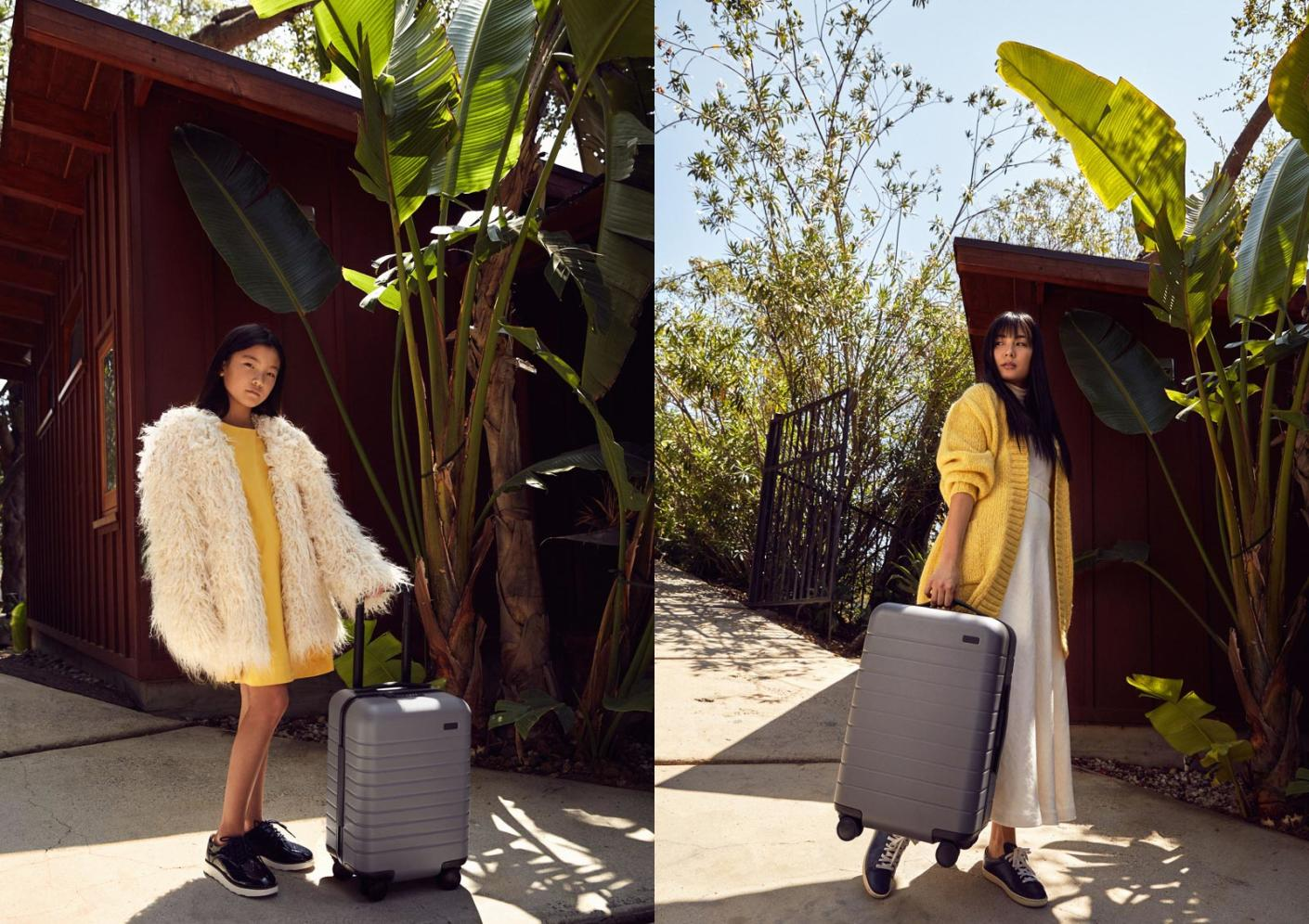 On the left is a young girl in a beige trench coat holding The Kid's Carry-On in Sand by its handle and standing in front of green bushes.  On the right is a woman in a long beige coat holding The Bigger Carry-On in Sand by its top handle and standing in front of a green bush.