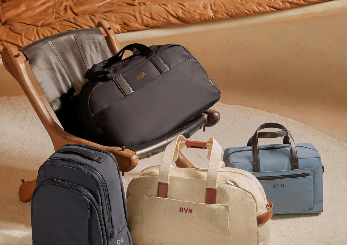 Away travel bags with a black Weekender on a chair, one in sand and coast on the floor with a navy backpack.