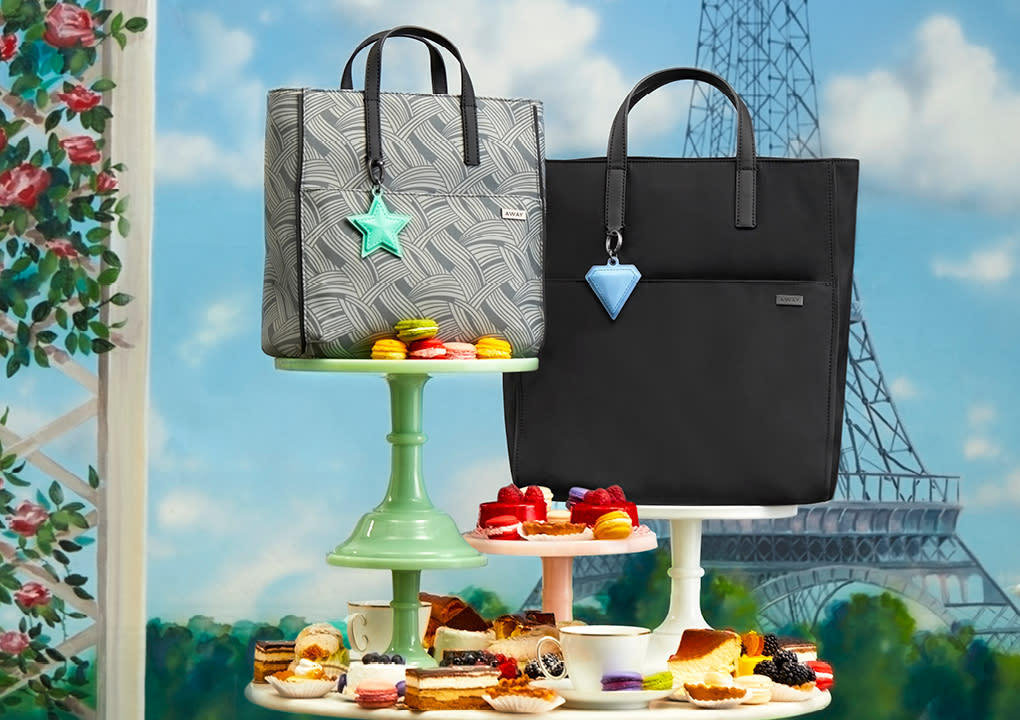 Away Tote shoulder bags in grey and black displayed on food servers with dessert against a background of the Eiffel tower.