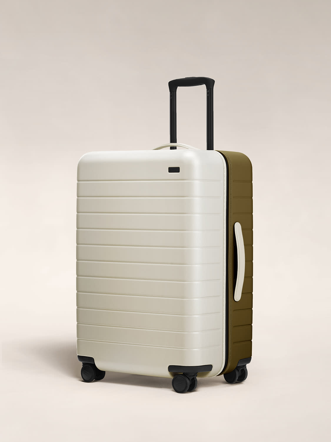Angled view of the Medium hardside suitcase in Beige/olive