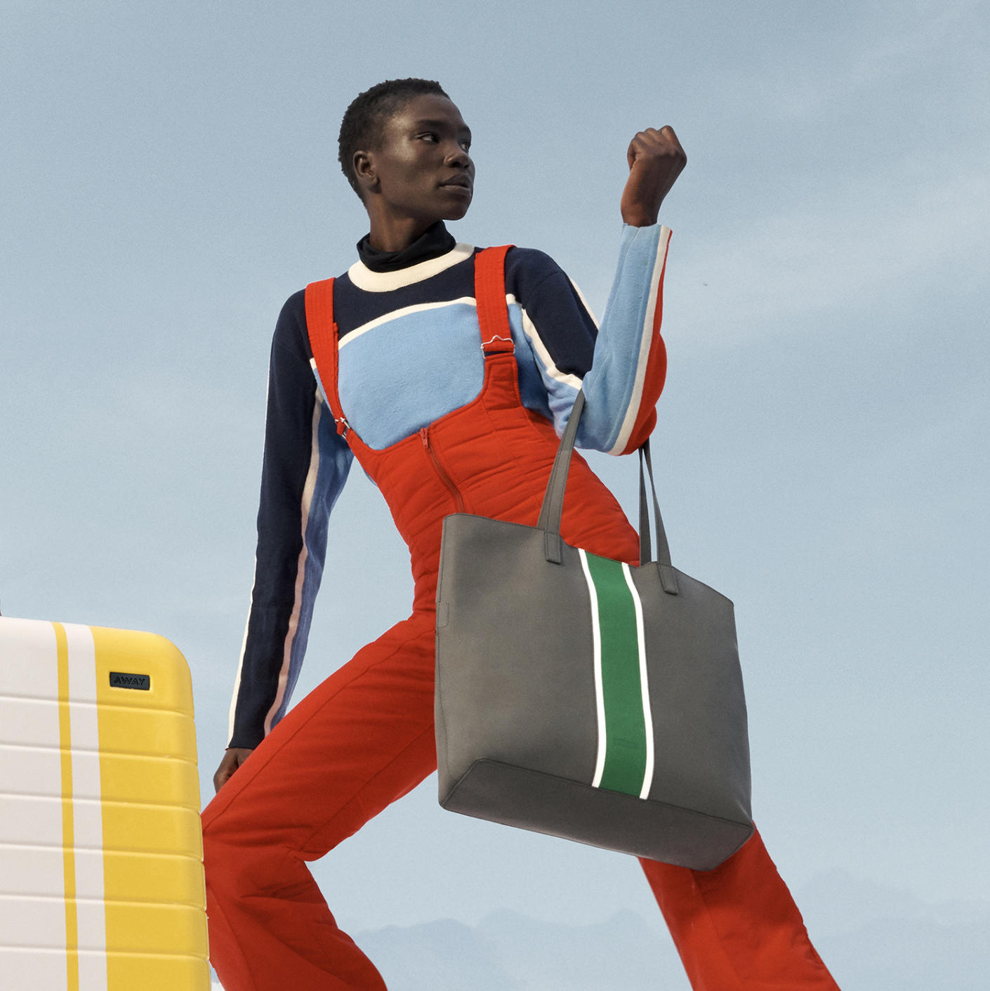 A woman with an Away Chalet Collection-yellow carry-on suitcase with a white stripe and grey tote bag with green stripe.