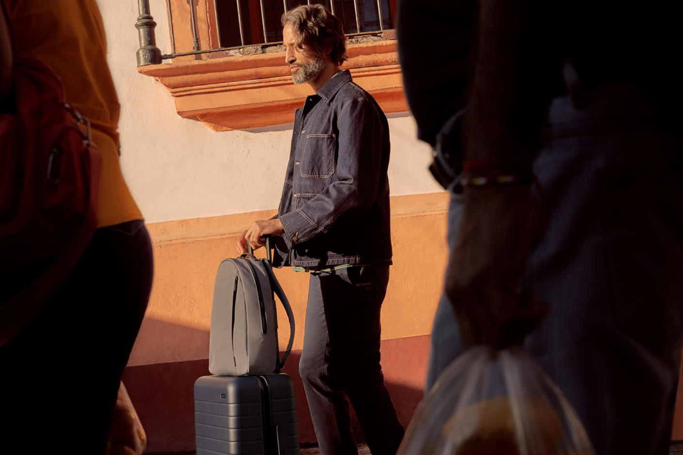 A man in a denim jacket rolling his carry-on suitcase and backpack on a cobbled street.