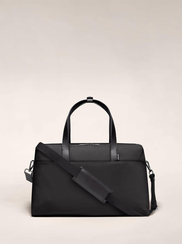 Large shoulder bag in black with raised handles and shoulder strap across the bag.