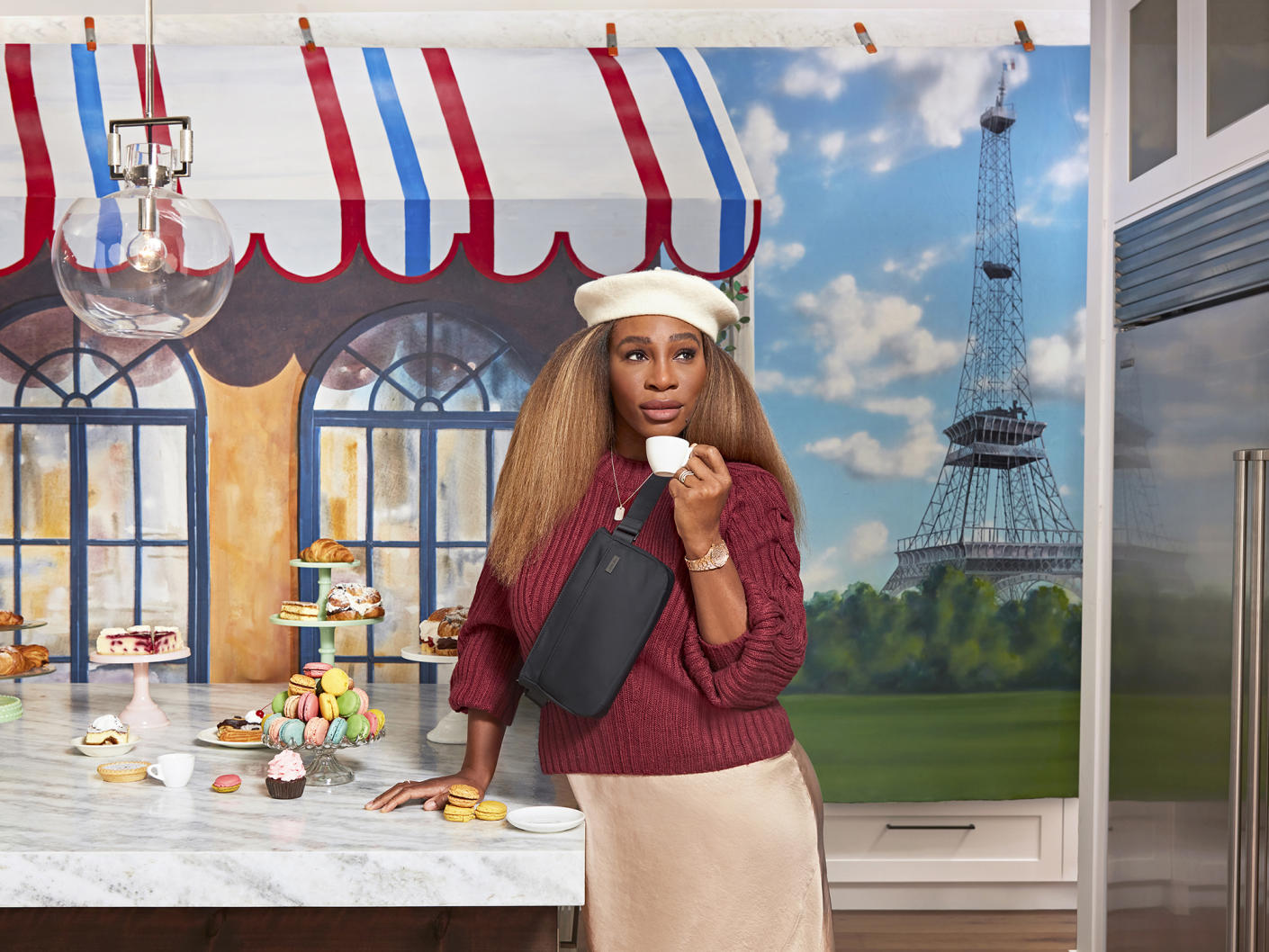 Serena Williams sipping a cup of coffee outside a cafe wearing a crossbody travel bag and Eiffel tower in the distance.