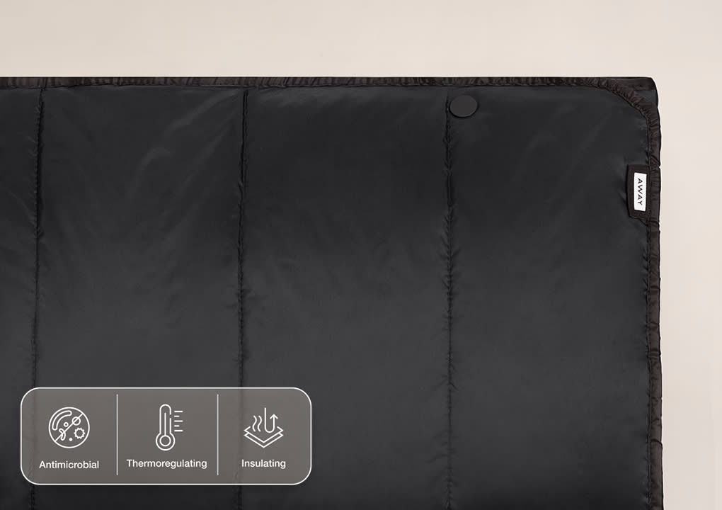An Away travel blanket in black laid flat to show seams.