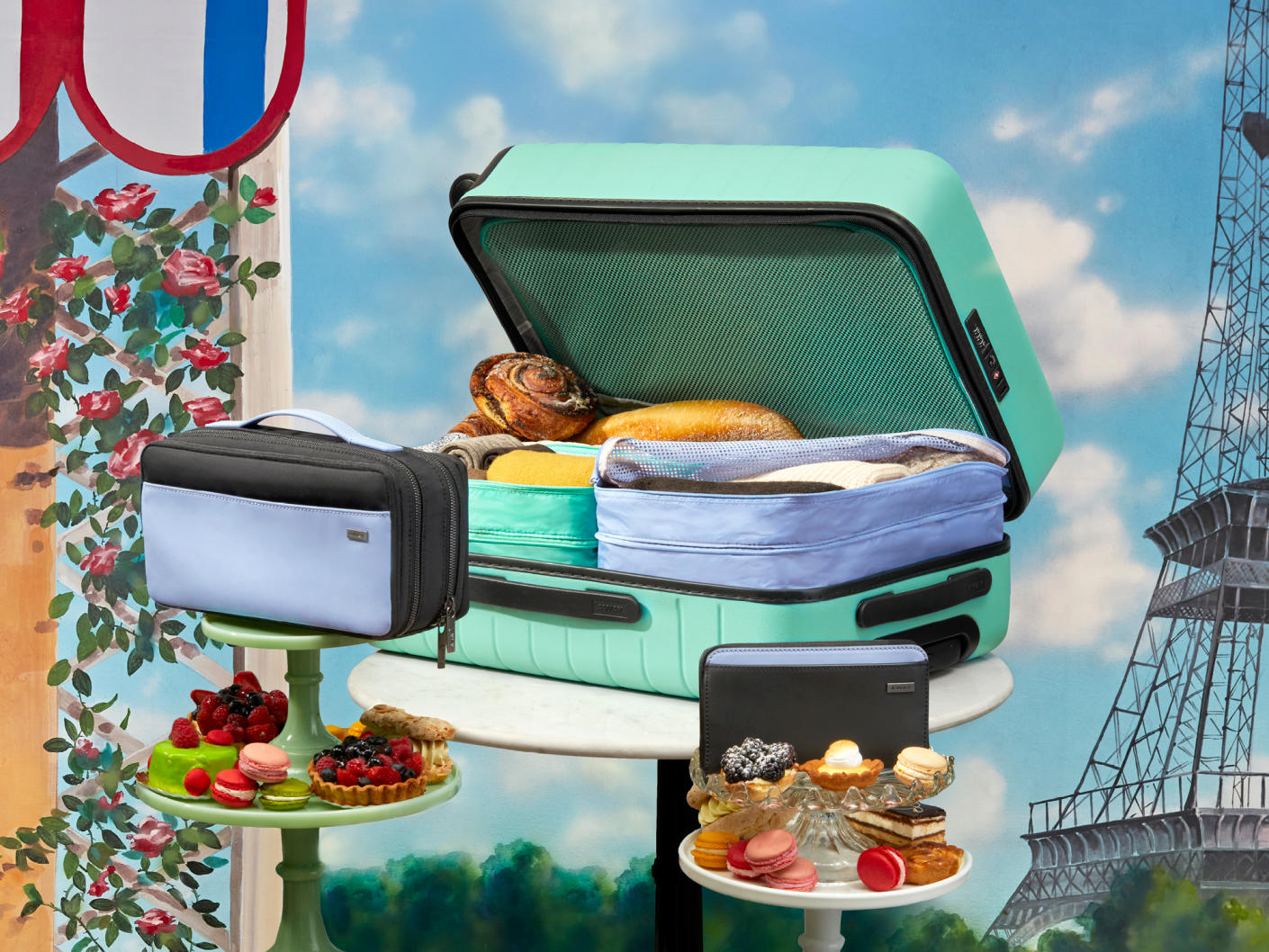 A sea green suitcase packed with picnic food, Away travel organizers displayed on platters with dessert with the Eiffel tower in the background.