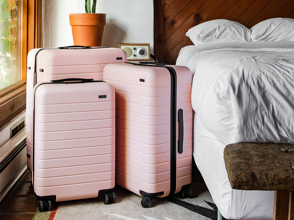 three blush suitcases in carry on and checked sizes perched next to a white bed.