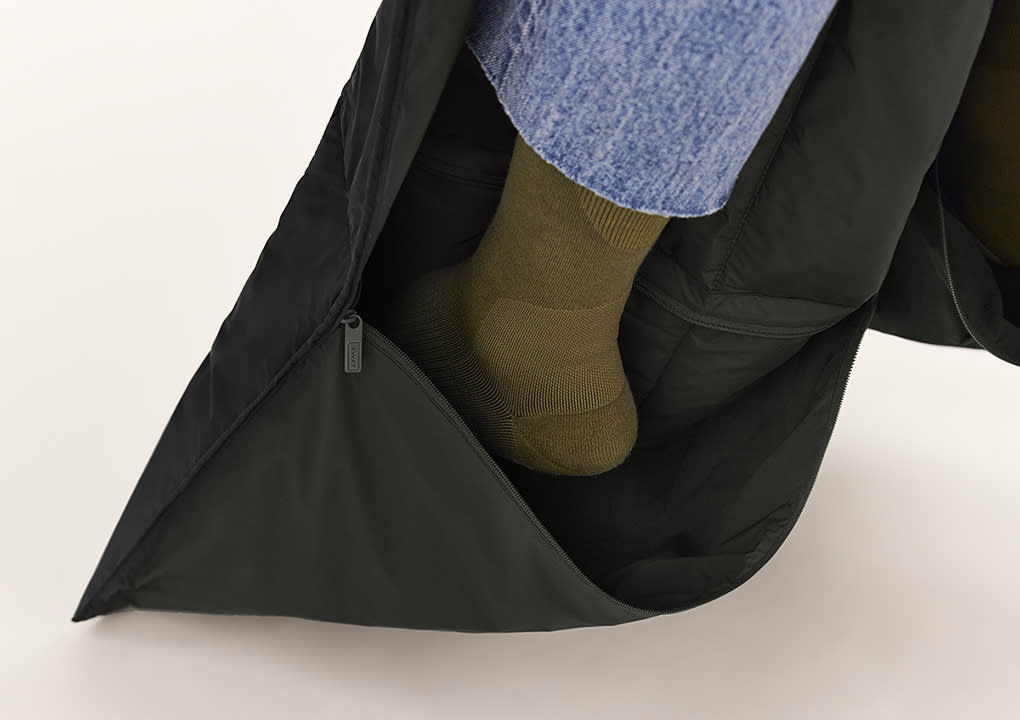 A foot shown inserted into the pocket of a travel blanket.