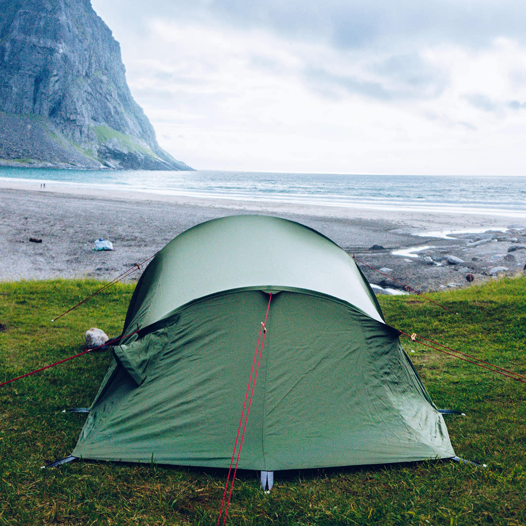 A green beach camping tent set up near the water with a sea cliff in view.