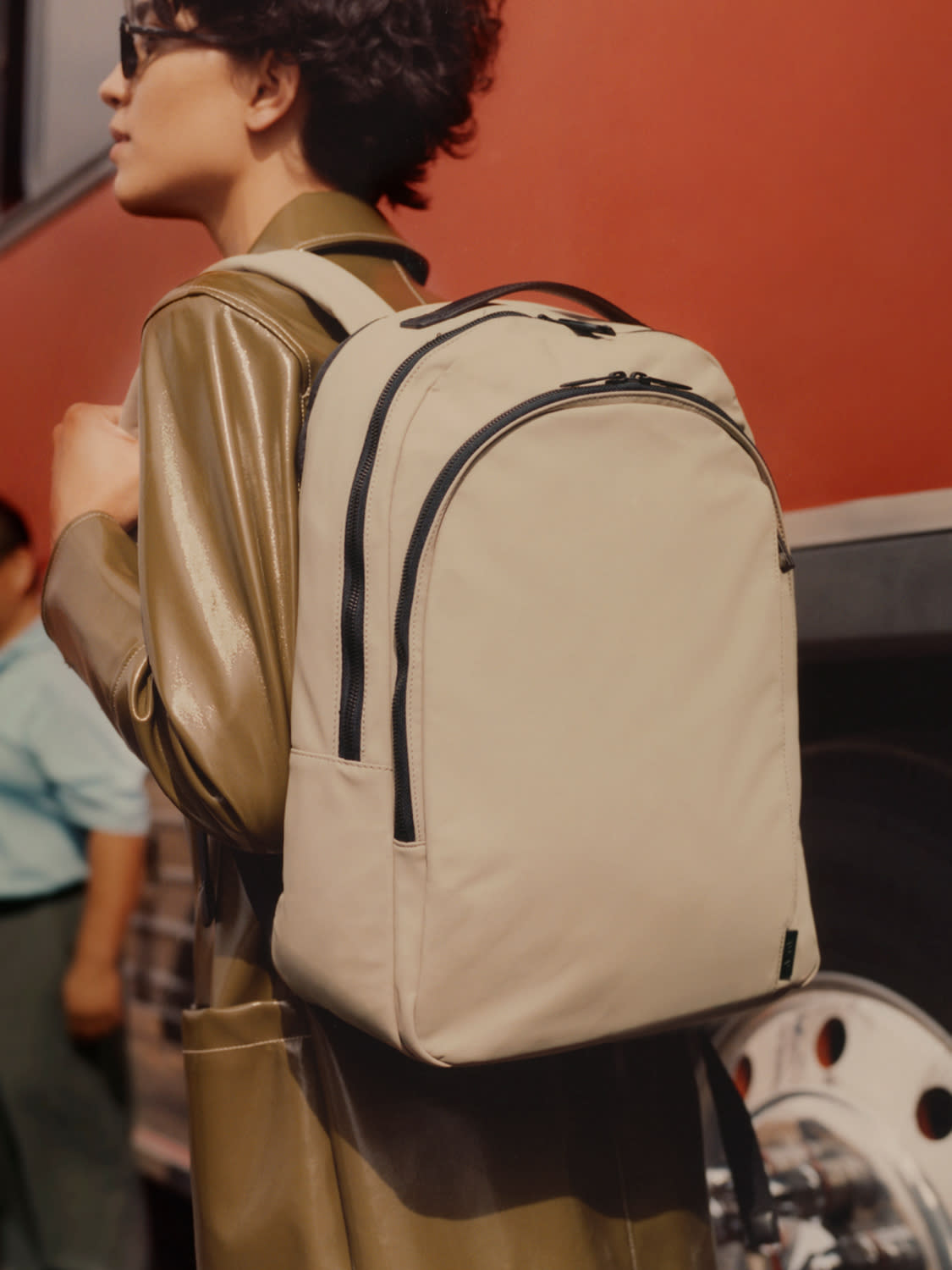A woman with a sand color backpack on her shoulder.
