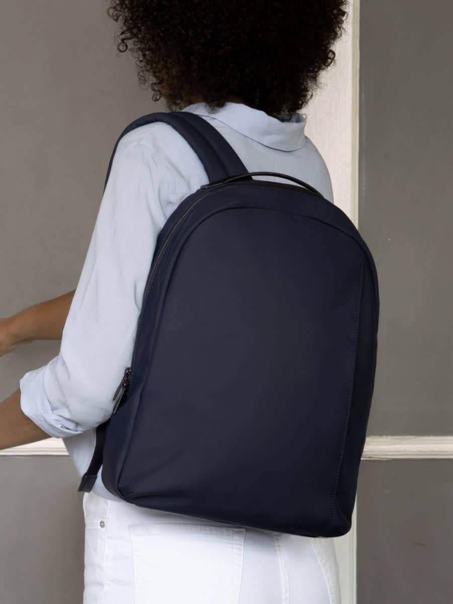 A woman wearing white pictured from the back with the Away navy daypack over one shoulder.
