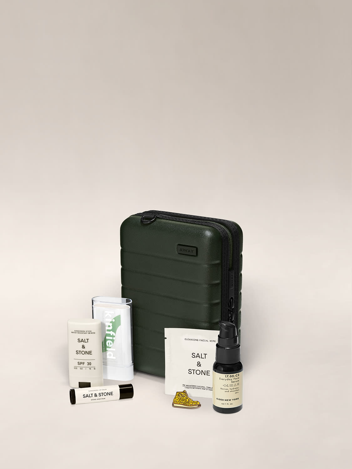 Mini suitcase in green shown behind a bottle of bugspray, face serum, sunscreen stick, lip balm, facial wipe and pin.
