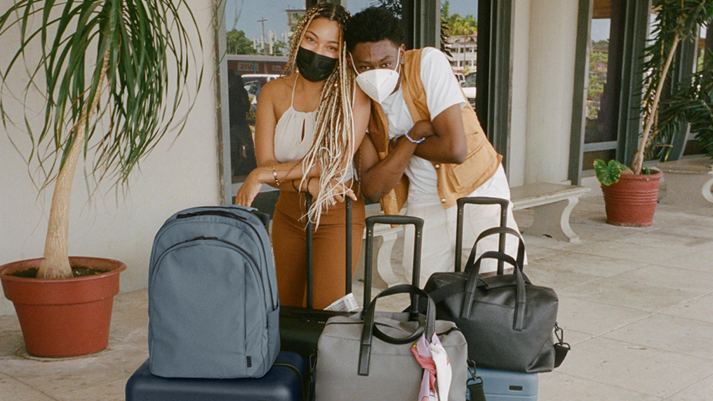 Two friends standing behind travel suitcases and bags - cropped 16x9