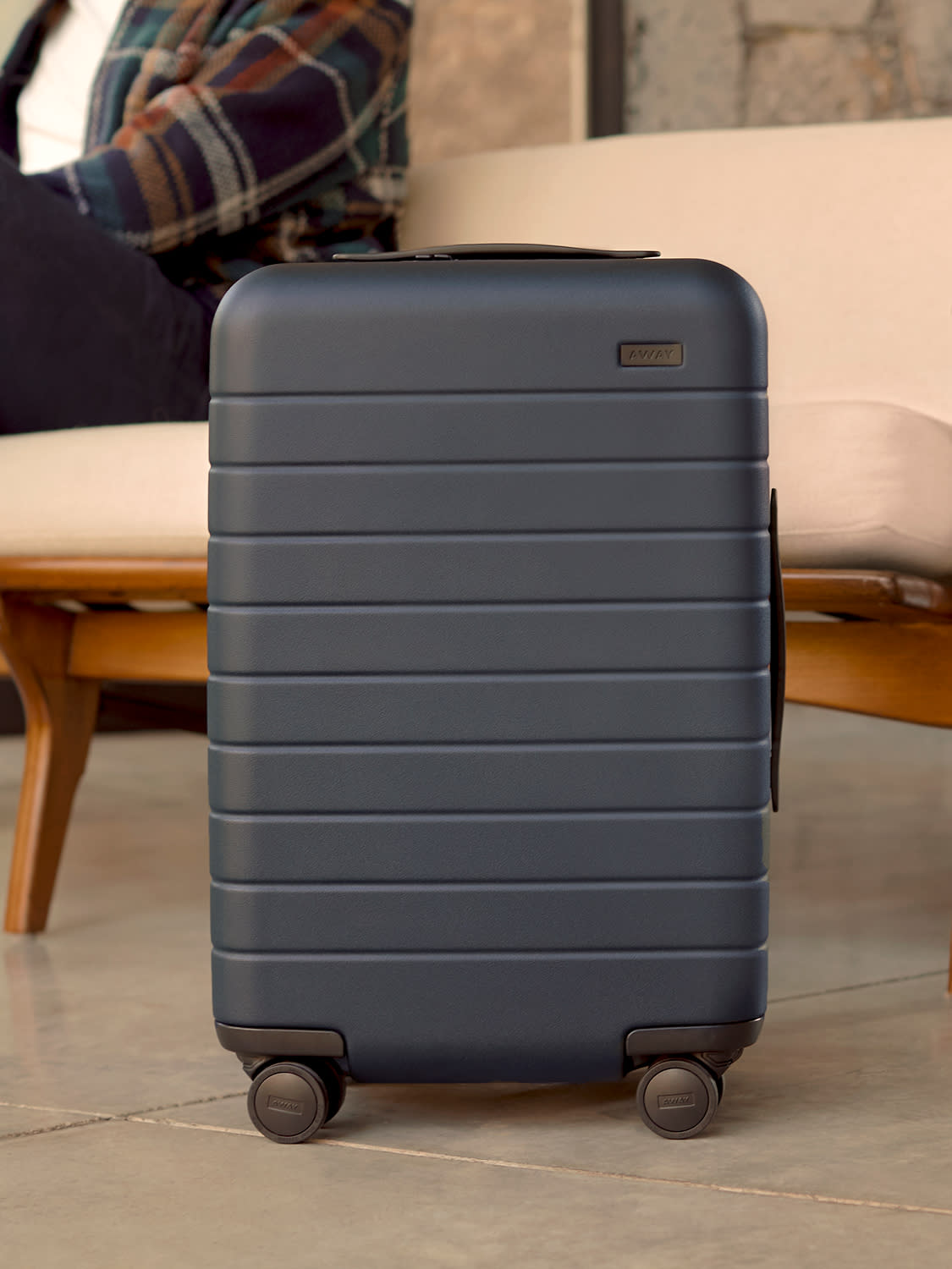 A man sitting on a bench behind his carry-On suitcase in navy blue.