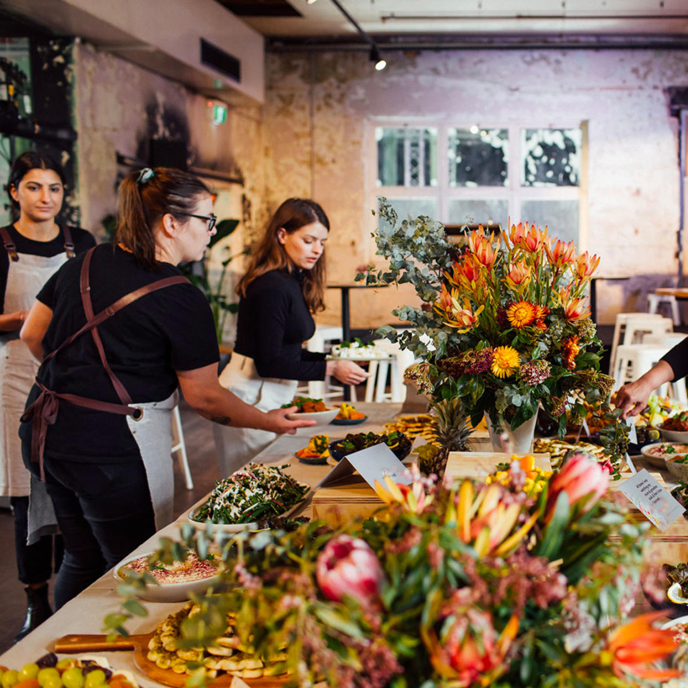 Three people setting up an assortment of food and flowers on a long dining table