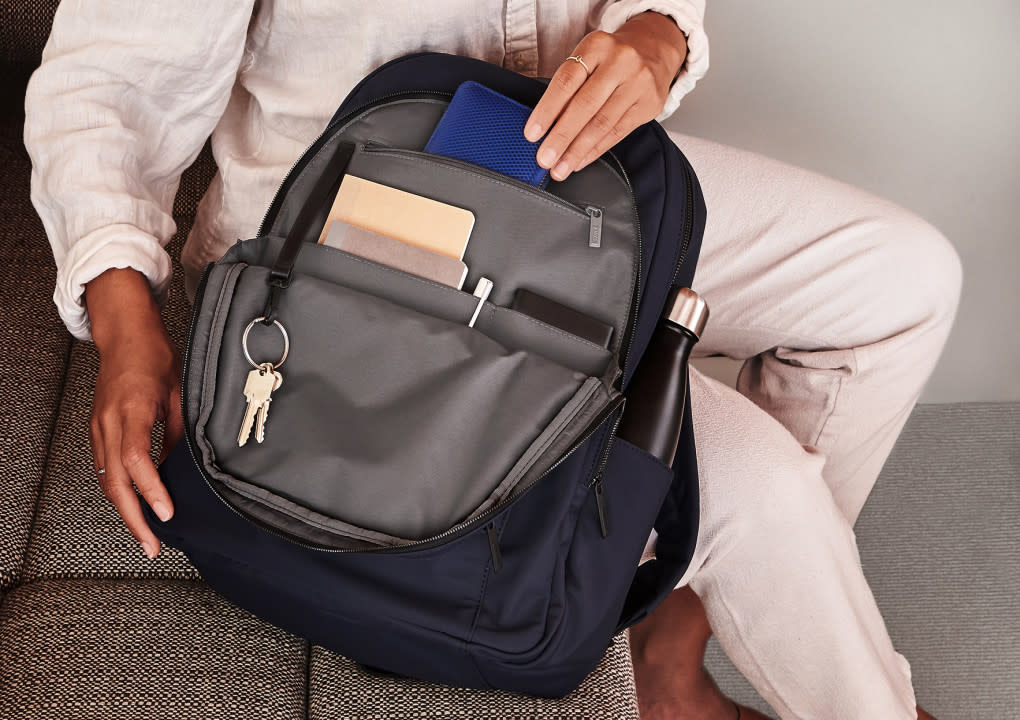 Someone grabbing a wallet from the interior pocket of an open backpack.
