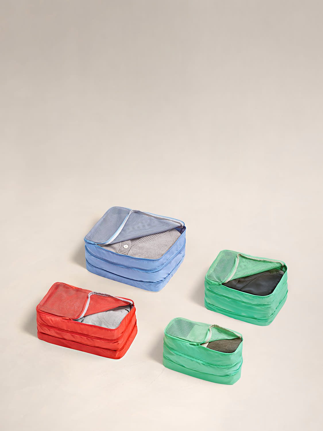 The Expandable packing cubes set of four in periwinkle, aqua and coral