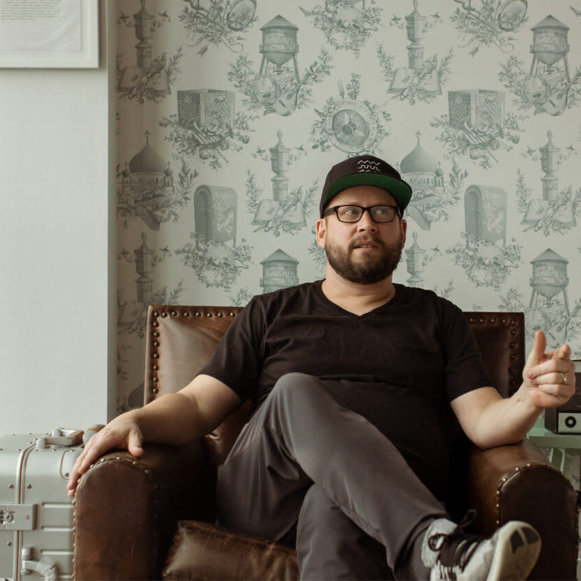 Dallas Taylor, podcast host in a black t-shirt sitting on a sofa, legs crossed.