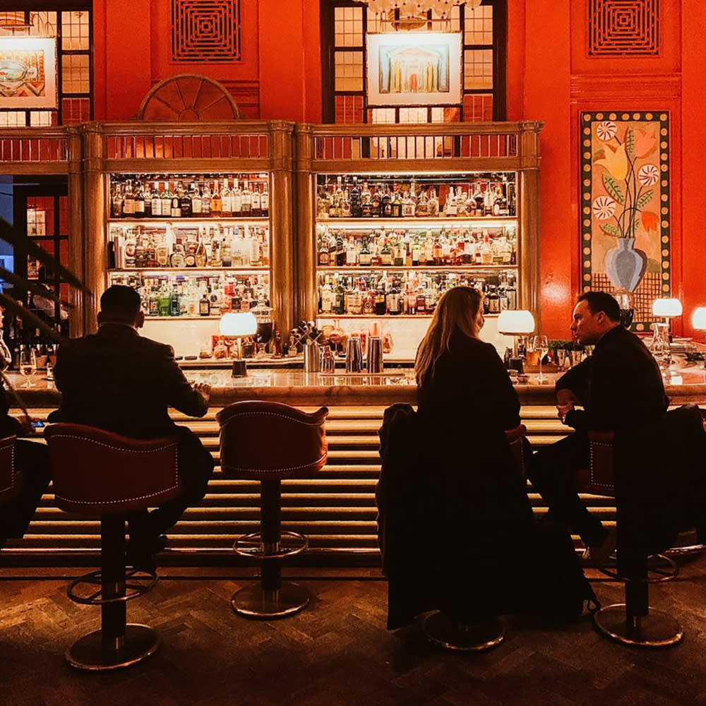 People sitting at a London bar with a display of liquor bottles against a dramatic wall of red.