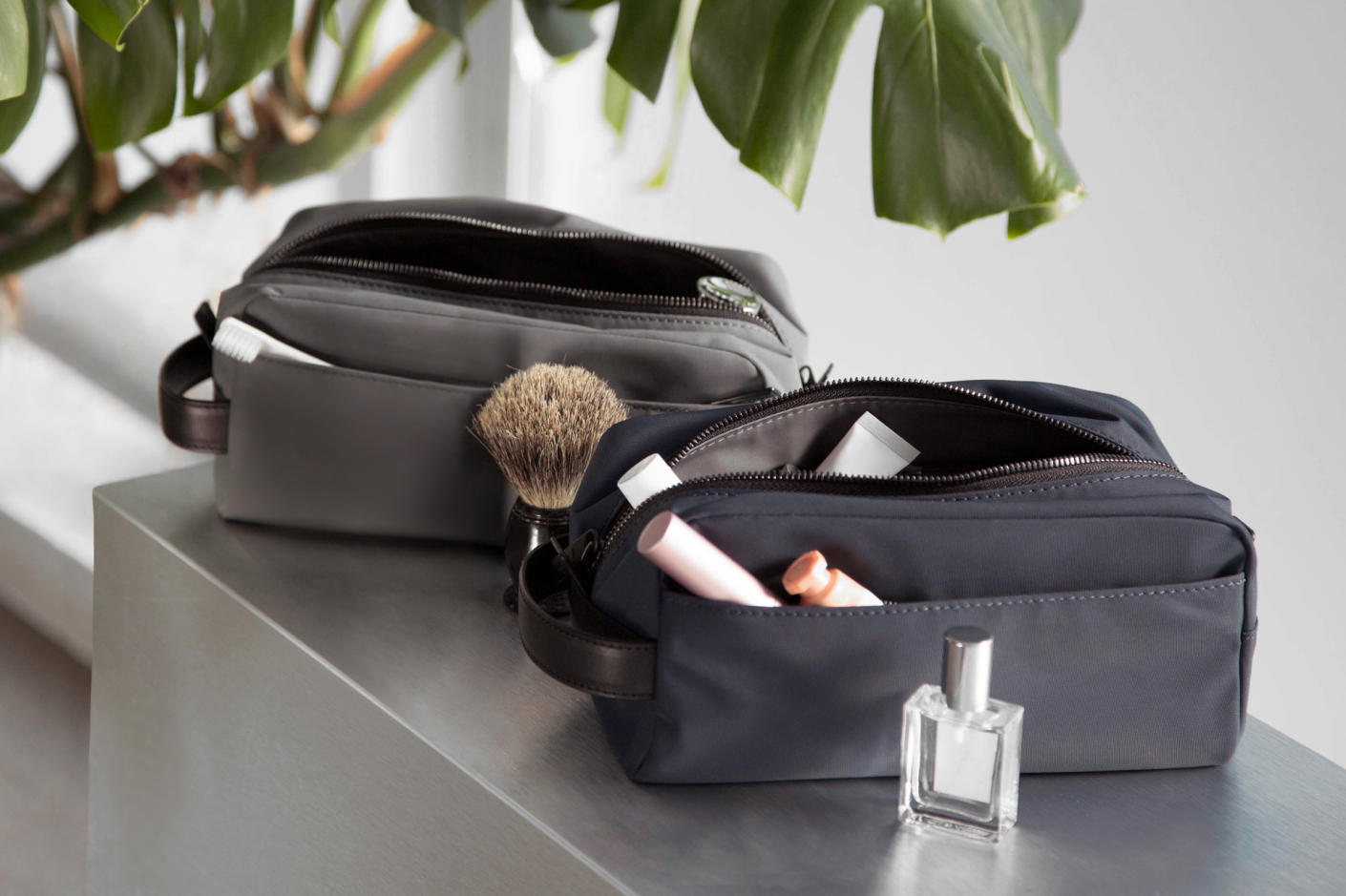 Dopp Kits in Black and Asphalt sitting on a counter with various beauty and grooming products in and around the Dopp Kits.