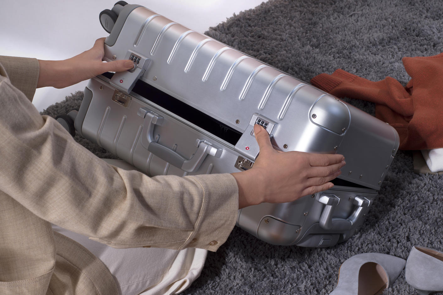The Aluminum Bigger Carry On on its side showcasing TSA  approved combination locks and no zippers.