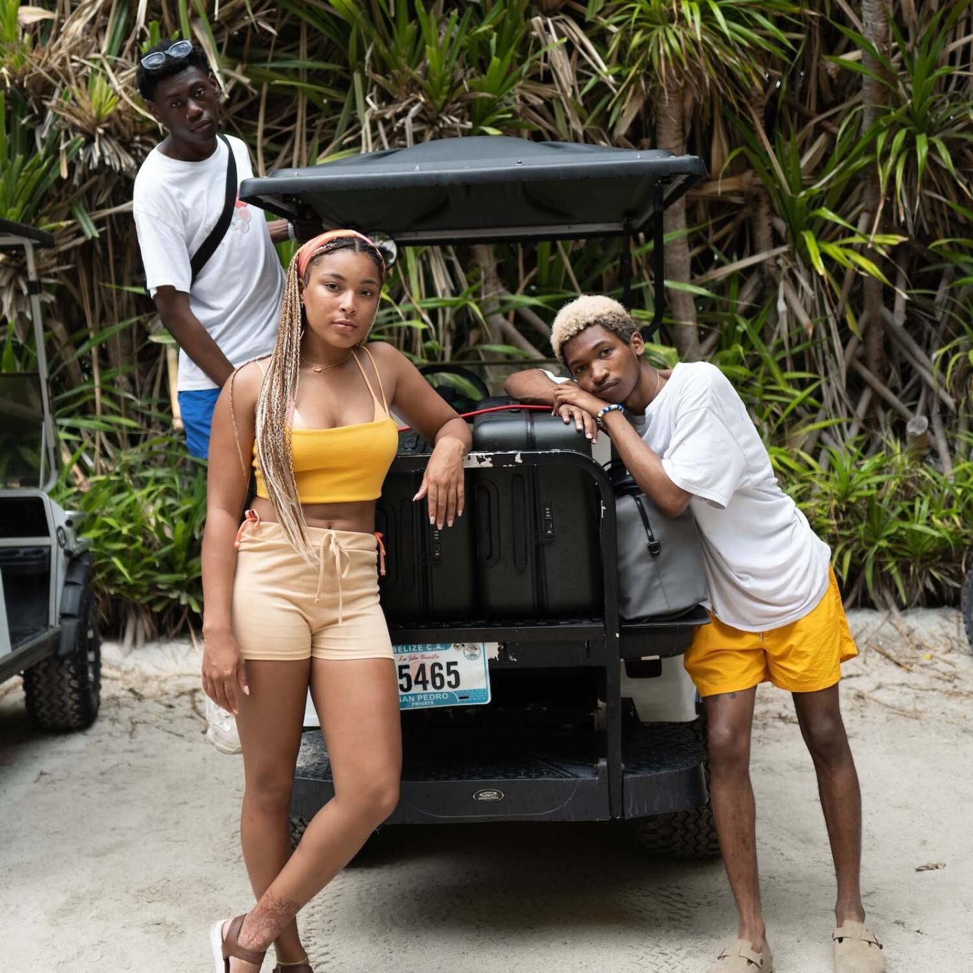 Two travelers in Belize standing beside two Away suitcases on a golf cart