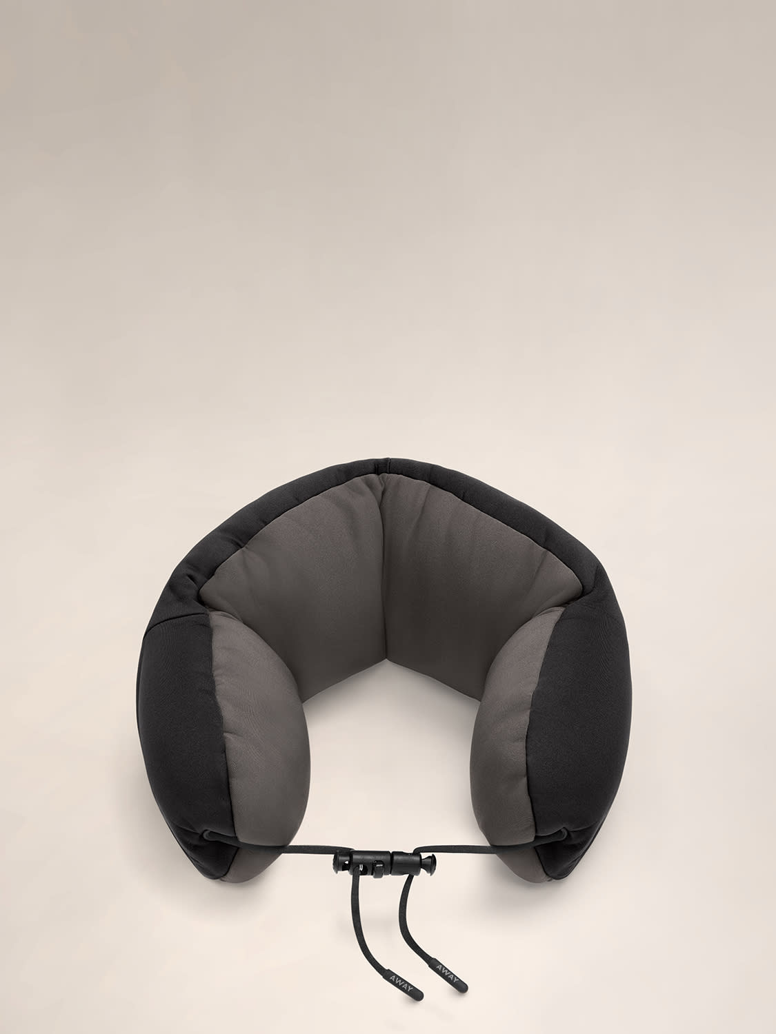 Aerial angled view of a black and grey travel neck pillow with a string loop on one side.