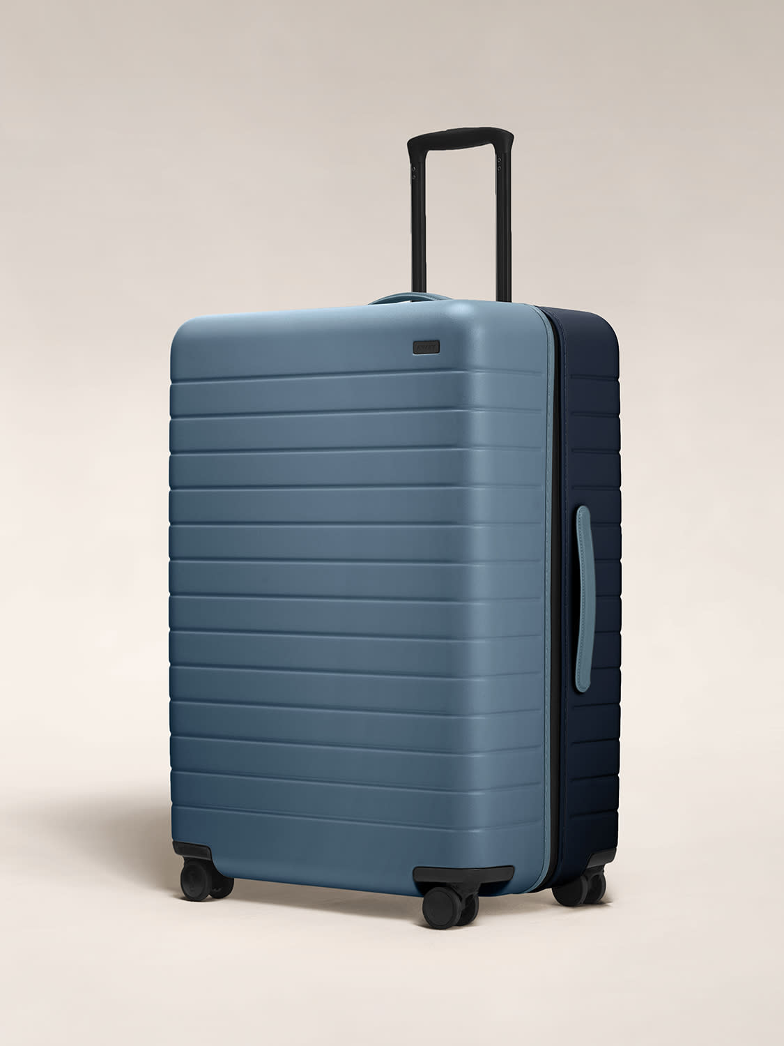 Angled view of The Large hardside suitcase in Coast/Navy