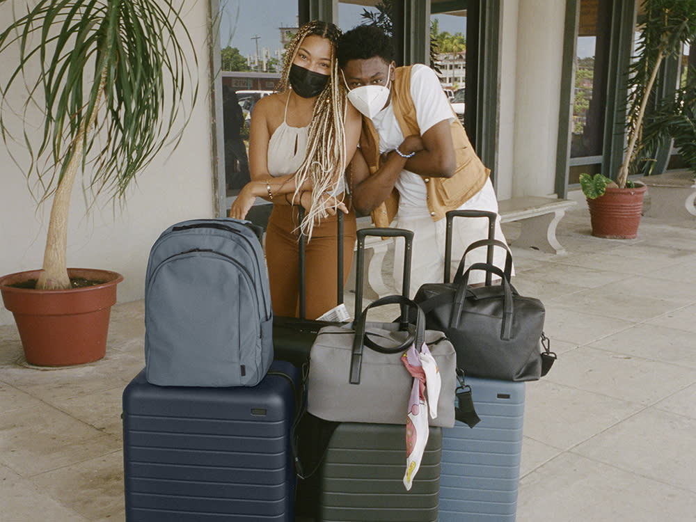 Two friends standing behind travel suitcases and bags