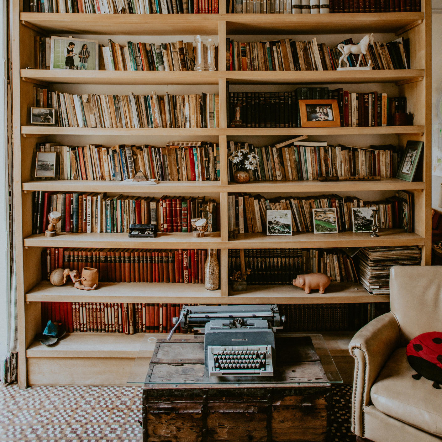 A double shelf with books and picture frames, with a couch and table with a typewriter in front of it.