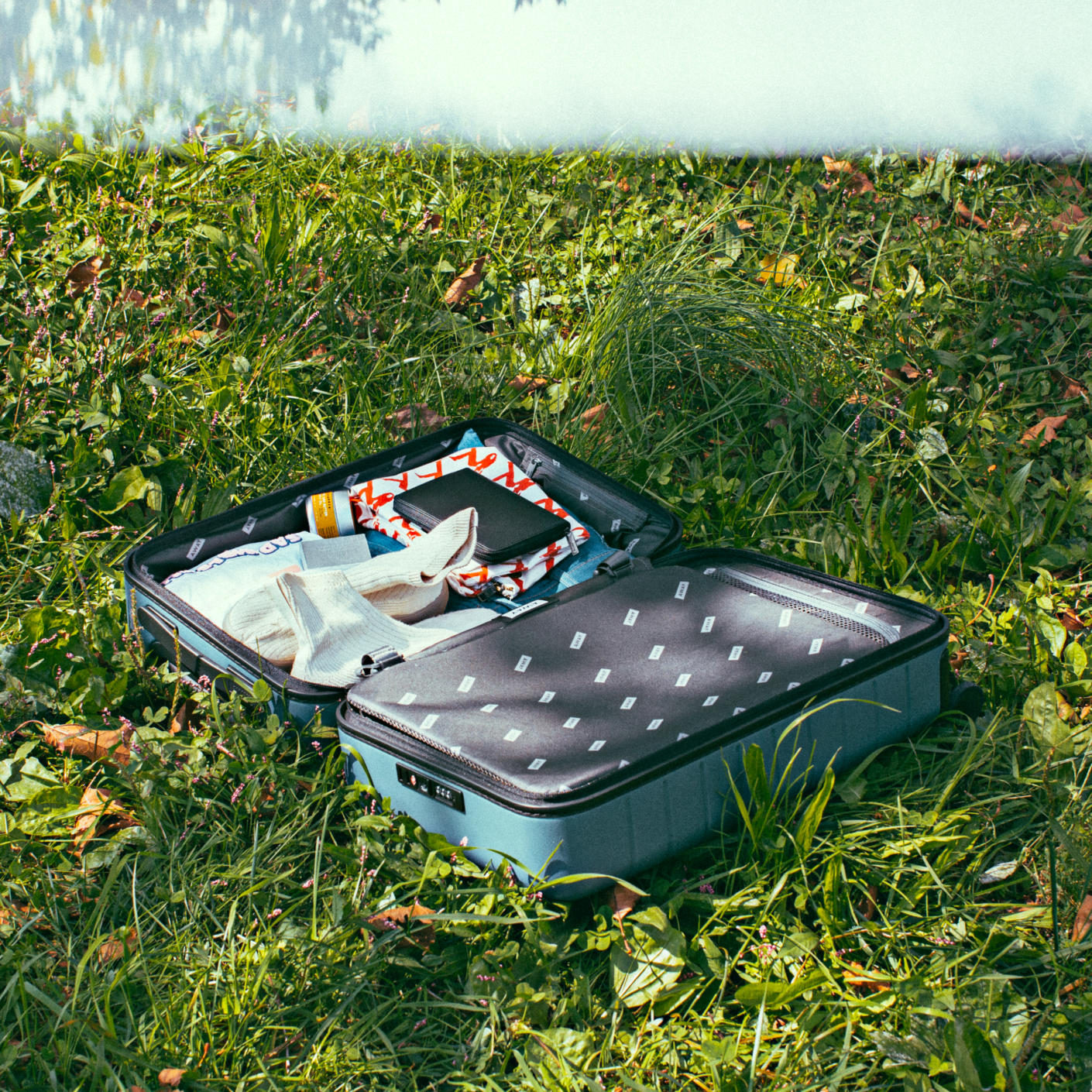 An open blue carry-on suitcase open in the middle of a grassy ground packed with internal compression showing.