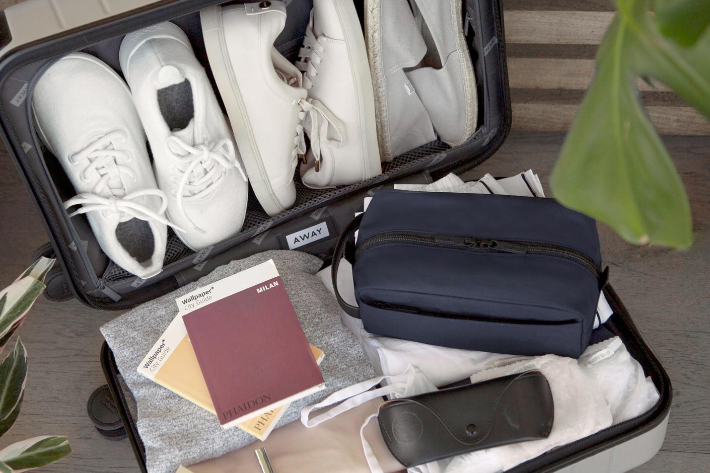 A closed Dopp Kit in Navy sitting on top of an open and packed suitcase.