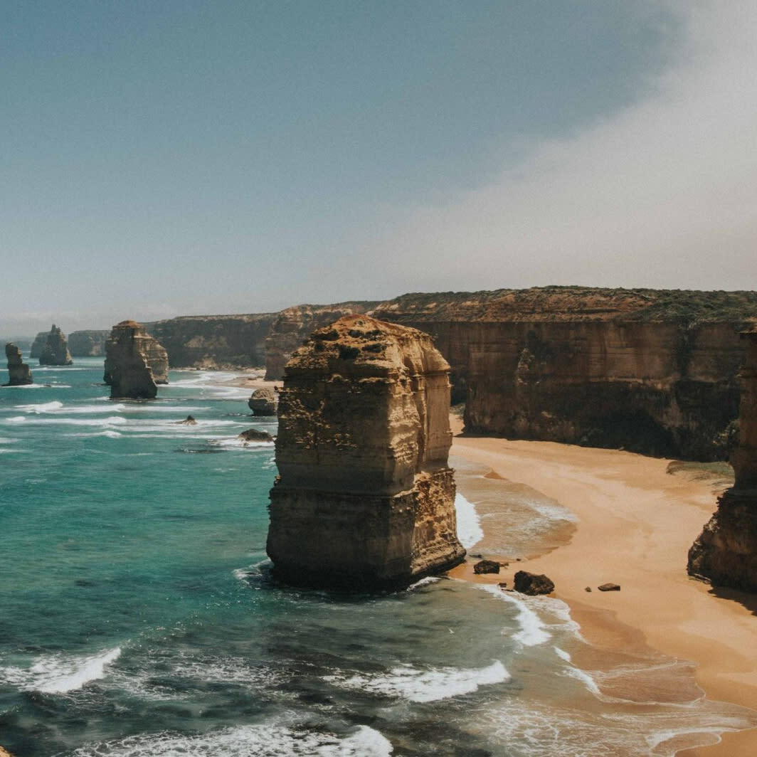 Dramatic cliffs and crumbling pillars of the Twelve Apostles (Australia) set against the ocean.