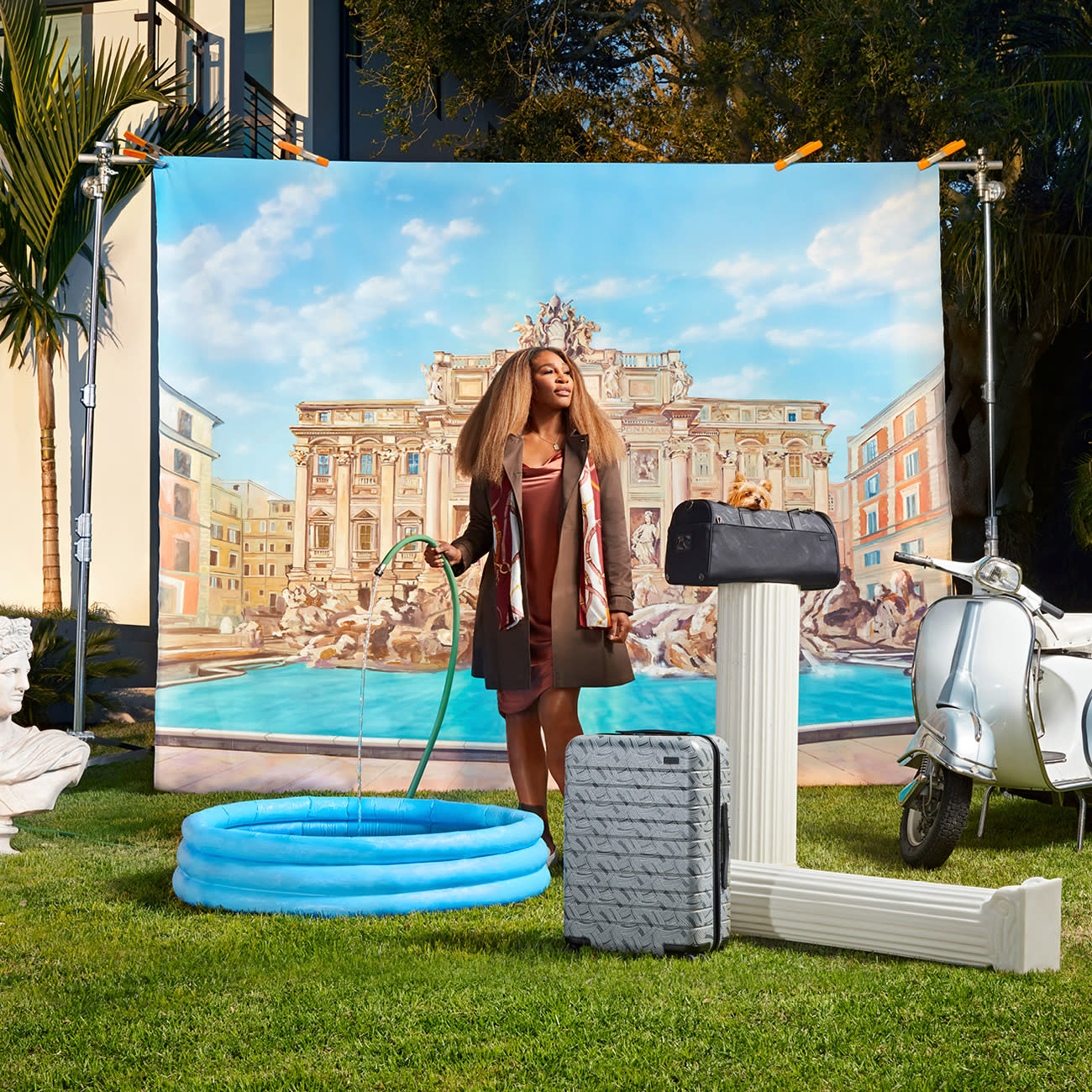 Serena Williams gazing in the distance with a hose filling a blue inflatable pool in her hand, a grey Away carry-on suitcase and a pet carrier displayed on a column.