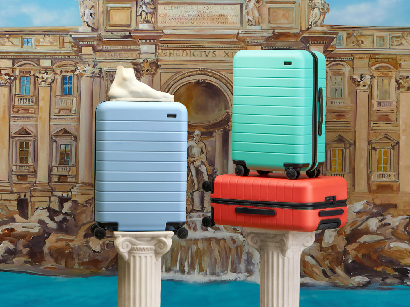 Three Away suitcases in red, light blue and sea green on two columns with The Trevi Fountain in the background.